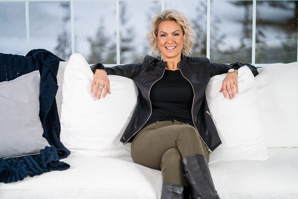 Stacy Raske sitting on a white couch.